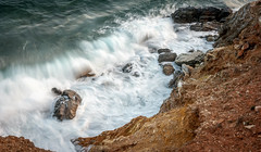 Crushing Waves & Rocks (Nick Panagou) Tags: longexposure blue light sea orange cliff seascape storm nature water rock contrast landscape rocks waves outdoor shoreline dramatic greece serene waterscape thessaly flickrsbest bestshotoftheday canon400d flickrbest bestphotographer canonefs1855mmf3556isii