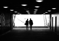 Guided by the uneven pattern (mkorolkov) Tags: street shadow blackandwhite sunlight monochrome silhouette walking lights couple pattern walk streetphotography tunnel fujifilm lamps xe1 xc50230