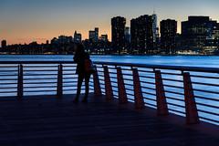 Everyone Enjoys the View (Torsten Reimer) Tags: nyc newyorkcity longexposure sunset sky usa newyork water river us sonnenuntergang skyscrapers unitedstates manhattan unitedstatesofamerica silhouettes eastriver northamerica railing gantryplazastatepark