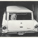 Smiling dog sits in back of Ford Falcon station wagon