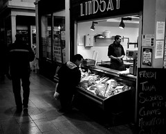 Fish Shop In The Grainger Market - Newcastle. (Richard James Palmer) Tags: street new uk portrait england urban blackandwhite white abstract black art 120 mamiya film monochrome newcastle photography trapped shoot gloomy iso400 fineart north streetphotography documentary overcast rangefinder gritty ishootfilm tyne east iso 1600 ilfordhp5 400 walkabout epson hp5 medium format analogue pushed melancholy northern northeast ilford f4 isolated upon iso1600 newcastleupontyne 1125 1600iso 80mm tyneandwear 2016 v700 mamiya7ii microphen filmisnotdead 7ii ilfordmicrophen epsonperfectionv700