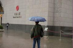 who's laughing at my umbrella hat now??? (gavingmb) Tags: china street urban storm man wet hat rain umbrella 50mm nikon central bank running hong kong suit f18 fx boc