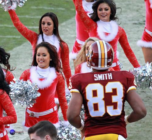 Redskins LB Preston Smith runs past Redskinette Cheerleaders.