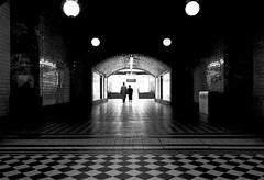 Passage (CoolMcFlash) Tags: bw blackandwhite blackwhite people silhouette tunnel tube passage contrast hütteldorf subway station vienna austria canon eos 60d sigma 1020mm 35 floor light walking hat couple sw schwarzweis personen umris kontur durchgang kontrast ubahn wien österreich streetphotography street boden licht gegenlicht gehen hut paar fotografie photography schachmuster mantel coat architektur symmetry symmetrie bnw