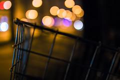 A basket of bokeh (thethomsn) Tags: city detail art bicycle night germany dark lights blurry soft moody dof basket traffic bokeh streetphotography depthoffield sidewalk korb wideopen 30mm primelens bokehlicious thethomsn