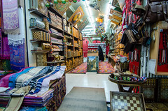 Store in the Souk (Tex Texin) Tags: shop booth colorful crafts middleeast jewelry souk vendor cloth rugs oman seller muscat muttrah mutra
