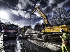 Digging out the Canal (Luc V. de Zeeuw) Tags: trees house water netherlands yellow clouds truck canal mud digging smoke helmet denhaag smoking worker splash trafficsign excavator zuidholland