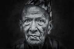 Old man with topi hat (Axel Halbgebauer) Tags: street nepal portrait people face hat closeup blackbackground zeiss dark prime back intense eyes lowlight head expression candid sony ngc culture naturallight oldman headshot 55mm age stare tradition tribe wrinkles pokhara topi southasia 6300 saarc sonyalpha