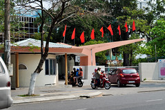 In and out (Roving I) Tags: trees children parents education transport flags vietnam scooters schools motorbikes pupils danang helmets entrances gateways