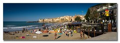 Cefal beach (Descended from Ding the Devil) Tags: blue sea sky people italy panorama beach umbrella bay town sand waves sicily fullframe lungomare lightroom cefal mirrorless photoborder sonya7mkii