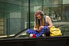 Colourful Character (Leanne Boulton) Tags: life street city uk light shadow portrait people urban man color colour detail male texture face fashion canon hair 50mm scotland living rainbow colorful sitting natural humanity outdoor expression glasgow candid character culture streetphotography style streetlife scene human shade 7d braids colourful society tone facial starsandstripes dyed individuality candidstreetphotography