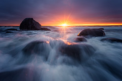 Last Rays (Arvid Bjrkqvist) Tags: ocean blue light sunset sea orange sun storm motion water yellow clouds evening coast rocks waves purple sweden stones horizon overcast final sunburst rays streaks sunrays nsbokrok