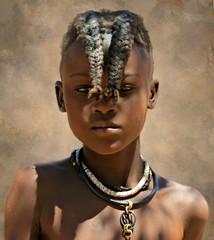 A young Himba girl wearing the pre-puberty hair style of two braids in front of the face. (Linda DV (away)) Tags: africa street travel portrait people cute nature face canon river children geotagged kid child candid young culture clothes kind ochre ethnic minority discovery enfant namibia himba ethnology worldtravel southernafrica travelphotography kaokoland travelportrait 2013 geomapped ovahimba minorit minderheid exploretheworld lindadevolder otjikandero otjize powershotsx40 picmonkey