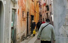 the many hues in an Italian lane (SM Tham) Tags: street windows people italy buildings outdoors town alley paint colours streetlamp pastel flags tourists cobblestones lane balconies walls windowshopping doorways lakeorta italianlakes ortasangiulio