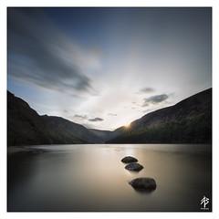 Glendalough (fearghal breathnach) Tags: longexposure ireland sunset sun lake water glendalough rays wicklow wicklowmountains leadinglines glendaloughlake