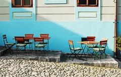Sighisoara, Romania (PM Kelly) Tags: street travel blue light summer sun bar table outside cafe chair cobblestone romania sighisoara transylvania