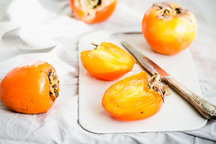 Fresh juicy persimmons on a light background, raw fruit (harmonyandtaste) Tags: autumn food orange white nature yellow fruit table asian dessert japanese wooden leaf juicy still healthy raw dish natural sweet background chinese pudding plate fresh canvas delicious persimmons exotic meal vegetarian tropical organic persimmon edible ripe nutrition kaki nutritious vitamin