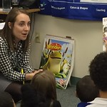 Students reading to elementary students in a classroom
