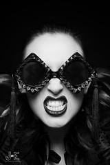 Grin it  JEP (James Eldridge Photography) Tags: light portrait monochrome face fashion female composition pose studio one mono glasses model nikon key exposure sister expression sinister teeth low feathers makeup lips portraiture pout stunning grin retouch powerful retouching