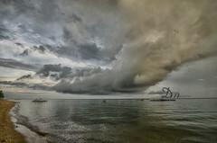 Only in Iloilo, Philippines. (danmocs) Tags: sea vacation sky cloud beach water rain boat fisherman iloilo