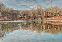 The Ice Divides (KC Mike D.) Tags: trees homes winter lake reflection clouds season pond