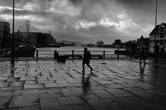 Homeward bound (halifaxlight) Tags: sea bw woman rain norway reflections walking cloudy pavement ships silhouettes sidewalk bergen bryggen pavingstones bergenfjord