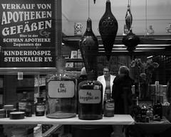 Die Apothekerin (carlosromonbanogon) Tags: street people bw white black glass samsung pharmacy amateur pharmacist medicines clients nx10 aphoteken