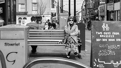 Chillaxing (Howie Mudge LRPS) Tags: road street uk travel windows portrait people urban blackandwhite bw woman man men travelling monochrome sign wales architecture female buildings bench outside outdoors mono glasses blackwhite chair women doors sitting pavement candid cymru bangor streetphotography streetlife bin panasonic sit shops casual posts gwynedd towncenter urbanphotography m43 mft micro43 microfourthirds mirrorlesscamera compactsystemcamera lumixgvario1442f3556ii micro43mountlenses panasonicdmcgx8