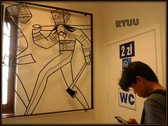 the tourist (Ryuu) Tags: door light shadow portrait man art window metal composition asian bars folk candid telephone profile toilet tourist smartphone human rails sculptures engravings mountaineers