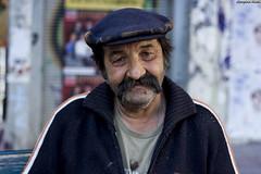 Paraskevas (Georgina ) Tags: portrait man candid character strangers streetphotography athens moustache chain greece shops stare wrinkles unshaved bluecap olderman bluejacket greekman interestingfaces