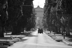 Peacebreaking (Elios.k) Tags: road camera city travel trees summer vacation blackandwhite bw italy travelling tourism monument monochrome cemetery horizontal canon outdoors photography memorial gate dof cross path tricycle perspective corridor entrance august nopeople depthoffield ape vehicle portal column salento puglia lecce piaggio unification apulia 2015 5dmkii