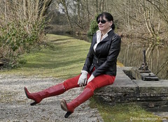 Lancashire Mills - 3/6 (Mistress Maggie dot com) Tags: red woman black sunglasses leather lady female outdoors glasses shiny stream sitting highheels pants boots shades jacket gloves mature satin mistress leggings dominatrix domina kneeboots patent gloved helmshoremill
