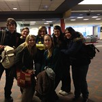 Students posing together in an airport.