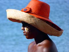 Nosy Kimba girl (J K Johnson) Tags: africa red portrait orange sun hot flower color texture girl face hat bronze interesting travels paint bright skin colorfull profile shade madagascar jimjohnson jkjohnson facepaintcolorful