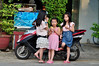 Sunday best (Roving I) Tags: street trees girls children eating stripes longhair motorcycles dressedup vietnam dresses dots danang sym apprehension breadrolls sundaybest banhmai ilobsterit