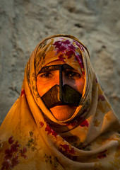 a bandari woman wearing a traditional mask called the burqa with a moustache shape, Qeshm Island, Salakh, Iran (Eric Lafforgue) Tags: portrait people woman sun face vertical outdoors persian clothing asia veil mask iran muslim islam religion hijab culture persia headshot hidden covered iranian adults adultsonly oneperson islamic traditionaldress burqa customs ethnicity middleeastern frontview persiangulf sunni qeshmisland burka chador hormozgan onewomanonly lookingatcamera burqua middleagedwoman   1people  iro straitofhormuz  colourpicture  salakh borqe boregheh irandsc03542