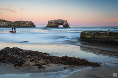 Natural Bridges State Park (lycheng99) Tags: california statepark pink sunset santacruz color reflections children sand rocks colorful waves play dusk bridges bluesky pacificocean pinksky pacificcoast naturalbridges rockformation naturalbridgesstatepark