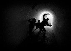 Shapeshifters (Fourteenfoottiger) Tags: street light people blackandwhite playing boys monochrome contrast pose dark children play darkness shapes silhouettes tunnel games shapeshifters