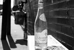 Water Bottle (John Bense) Tags: street city urban blackandwhite sun brick glass monochrome washingtondc bottle empty reflect shade brand noma