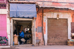 Artisan Shop (Simone Della Fornace) Tags: street city man color shop holding day sitting outdoor candid poor streetphotography photojournalism documentary lifestyle morocco marrakech medina journalism artisan dilapidated oneperson ethnicity