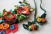freeform crochet statement necklace with red, pink, blue, and green crocheted flowers by irregularexpressions (irregular expressions) Tags: orange yellow purple burgundy crochet peach wearableart fiberart mahogany brightred textileart olivegreen crimsonred rainbowcolors emeraldgreen forestgreen crochetflowers grassgreen royalblue indigoblue freeformcrochet crochetflower ceruleanblue turquoiseblue crochetedflower crochetart magentapink irregularexpressions bibnecklace chartreusegreen statementnecklace fibernecklace statementjewelry oversizednecklace olivegreenleaf