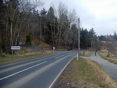 Southern entrance to Kingussie, 2016 Mar 23 (Dunnock_D) Tags: road uk trees sky cloud grass sign forest woodland grey scotland highlands cloudy unitedkingdom britain path highland roadsign cyclepath footpath bollard kingussie cycleway badenoch