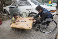 Ramesh plays a game know as Caram board with a local child (Handicap International UK) Tags: nepal earthquake kathmandu survivors disability