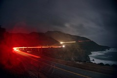 Once upon a time on a rainy night (PeterThoeny) Tags: ocean california street longexposure bridge light red sea water night coast highway raw pacific cloudy outdoor bigsur highway1 pacificocean lensflare flare mystical hdr californiacoast bixbybridge lighttrail waterdroplet concretebridge bixbycreekbridge photomatix fav200 1xp nex6 selp1650