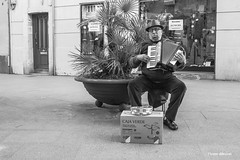 his life is dependent on a green box (dib, l'home dibuixat) Tags: street bw musician music man monochrome walking blackwhite waiting box accordion monochromatic blancinegre greenbox olympusdigitalcamera lhomedibuixat zuiko17mmf18 outbcn olympusomd5mii