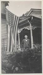 """Man stands on the porch next to a large American flag"""" (simpleinsomnia) Tags: old white man black monochrome vintage found blackwhite antique flag snapshot americanflag front photograph american porch vernacular frontporch foundphotograph"""