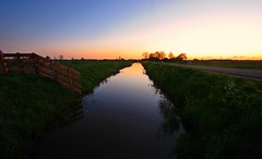 Sunset in the polder (M a u r i c e) Tags: road trees sunset sky nature water netherlands fence landscape horizon efs1022mm bethunepolder