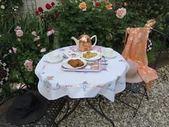 A moveable feast. Tea time in the garden with the flowers and the birds. (Traveling with Simone) Tags: pink flowers red roses plants cake table chairs tea outdoor cups apricot teapot gateau homebaked tarteauxpoires hom4emade soiedelyon