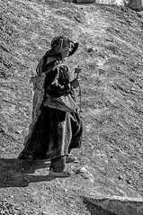 An Old Ladakhi Woman at Lamayuru (Anoop Negi) Tags: travel portrait woman india white black hat wheel rock outdoors photography photo dress path prayer goat rug kashmir anoop sedimentary bnw ladakh negi lamayuru ezee123