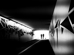 underpass (Sandy...J) Tags: street city light shadow people urban bw sunlight white black silhouette backlight germany dark underpass underground walking deutschland photography mono blackwhite noir fotografie grafitti darkness walk streetphotography atmosphere tunnel olympus menschen stadt sw monochrom passage atmosphre gehen gegenlicht dunkelheit unterfhrung spazieren sonnenlicht schwarzweis strase strasenfotografie